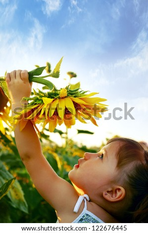 Beautiful little girl and sunflower - stock photo