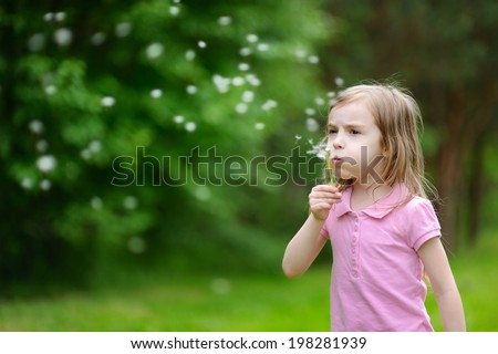 Beautiful little girl blowing a dandelion