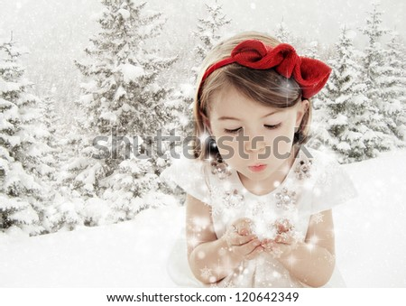 Beautiful little girl blowing snowflakes in white winter forest covered with snow