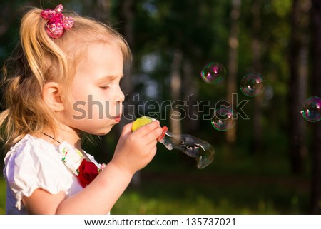 Beautiful little girl blowing soap bubbles in park outdoor