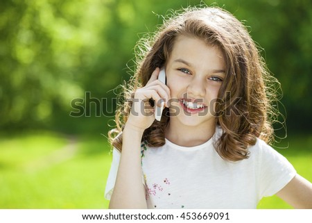 Beautiful little girl calling by mobile phone on the background of summer park