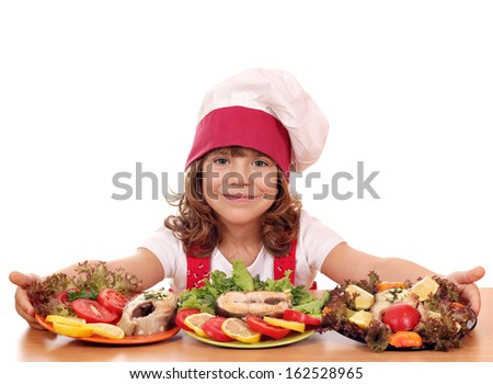 beautiful little girl cook with prepared salmon seafood - stock photo
