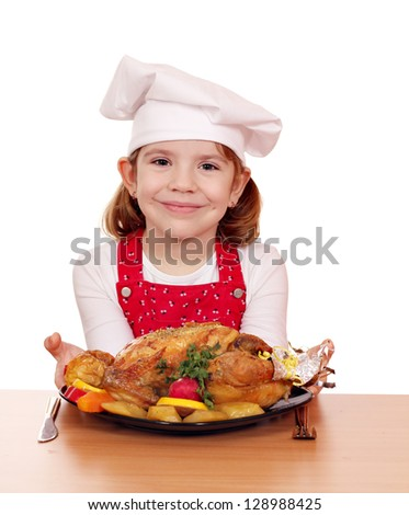 beautiful little girl cook with roasted chicken on table - stock photo