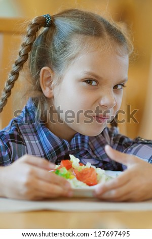 Beautiful little girl does not want to share meal in restaurant. - stock photo