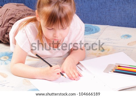 Beautiful little girl draws picture