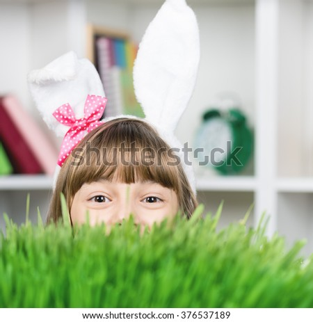 Beautiful little girl dressed in Easter bunny ears peeking from behind the green grass - stock photo