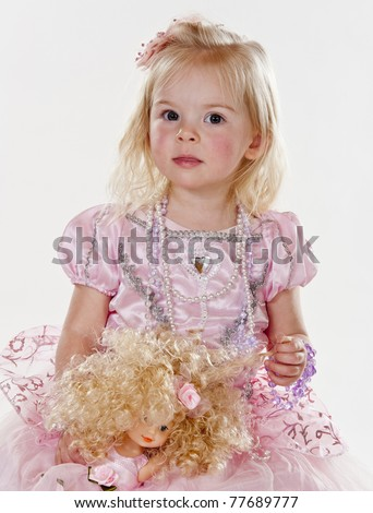 beautiful little girl dressed in pink fairy princess costume holding her doll against white background