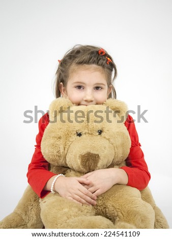 Beautiful little girl dressed in red playing with toy bear and posing with light grey background