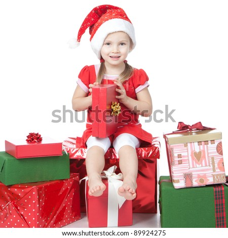 Beautiful little girl dressing in Santa's Helper hat with red gift over white - stock photo