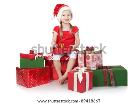 Beautiful little girl dressing in Santa's Helper hat with red gifts over white - stock photo