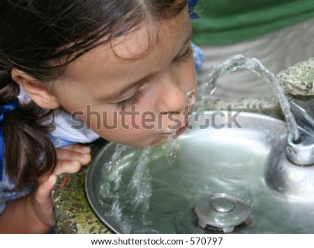 Beautiful little girl drinking water from a fountain. - stock photo