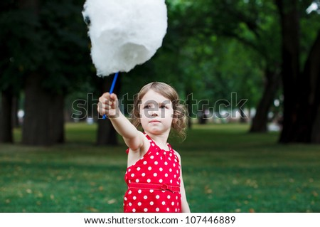 Beautiful little girl eating cotton candy in the park - stock photo