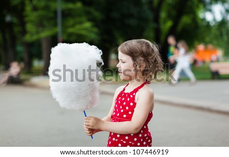 Beautiful little girl eating cotton candy in the street - stock photo