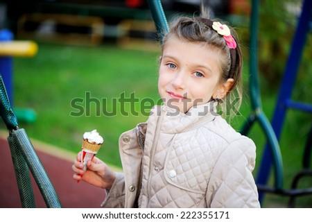 Beautiful little girl eats ice-cream at the warm autumn day - stock photo