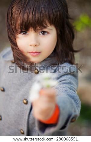 Beautiful little girl giving spring flower - stock photo