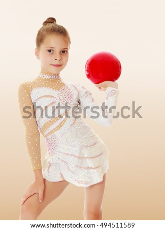 Beautiful little girl gymnast in elegant dress, posing with a red ball.On a brown background.