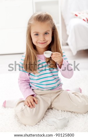 Beautiful little girl having a cup of tea playing with miniature tea set in her room - stock photo
