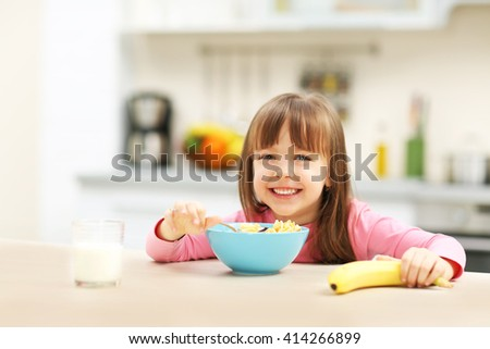 Beautiful little girl having breakfast with cereal, milk and banana in kitchen - stock photo