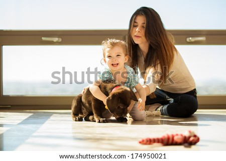 Beautiful little girl having fun and hugging his puppy at home - stock photo
