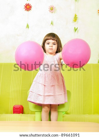 Beautiful little girl having fun with two pink balloons