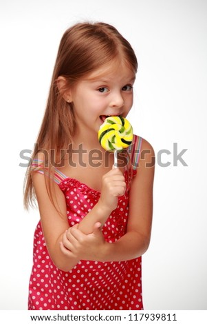 Beautiful little girl holding a big round swirl lollipop on Food and drink concept theme/Lovely little girl is posing on camera with candy - stock photo