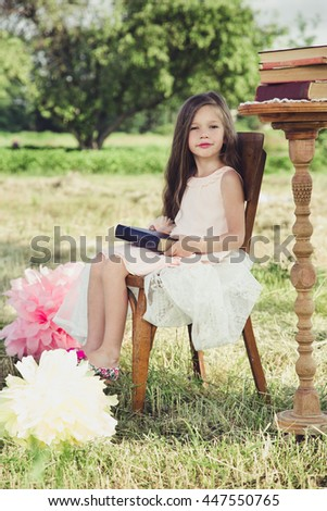 beautiful little girl holding a book in his hands. Around the nature - stock photo
