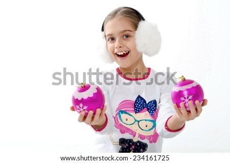 beautiful little girl holding a Christmas decorative pink balls for Christmas tree decoration / Smiley girl holding pink decorative balls. plays with toys - stock photo