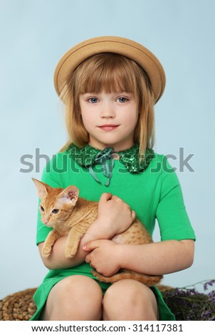 Beautiful little girl  holding a cute kitten. Blue background. Studio shot