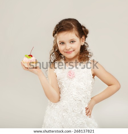 Beautiful little girl holding a delicious appetizing cake with cherry - stock photo