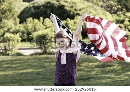 Beautiful little girl holding a large American flag in a sunny summer day in the park. Image with instagram filter.