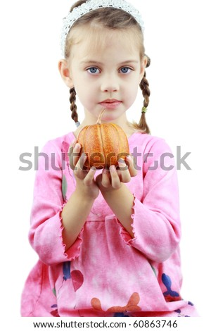 Beautiful little girl holds a pumpkin up to the viewer. - stock photo