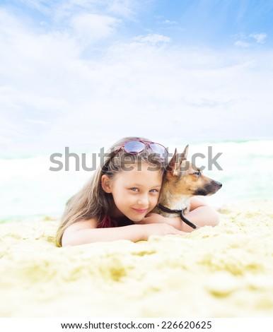 Beautiful little girl hugging her dog lies on the sandy sea beach - stock photo