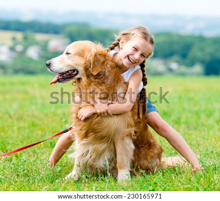 Beautiful Little girl hugging retriever in the summer park - stock photo