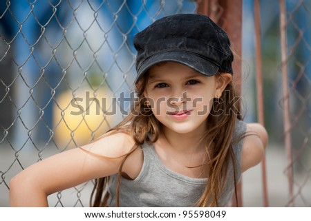 Beautiful little girl in a black cap on the street. - stock photo