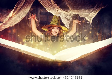 Beautiful little girl in a costume of witch in a wizarding lair. Halloween party. Halloween decorations. - stock photo