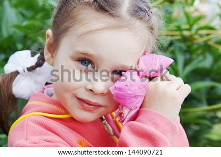 Beautiful Little Girl in a Garden with Peony Flower - stock photo