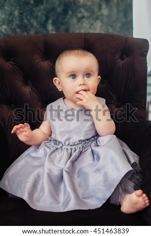 beautiful little girl in a gray dress sitting on chair