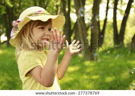 beautiful little girl in a hat on the nature - stock photo