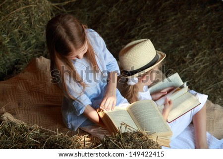Beautiful little girl in a hat sitting on the hayloft with a book to read and play - stock photo