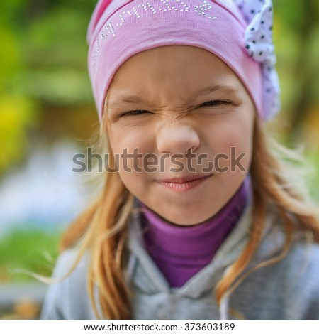 Beautiful little girl in a pink hat poses as a face. - stock photo
