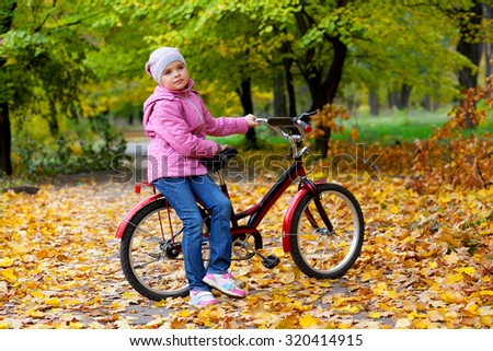 beautiful little girl in a pink jacket and hat leaning on a children's bicycle on an autumn background