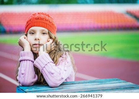 Beautiful little girl in a red cap and pink sweater in the stadium. - stock photo
