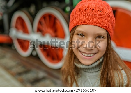 Beautiful little girl in a red cap near the old steam locomotive. - stock photo