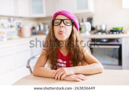 Beautiful little girl in a red cap sits at a table in the kitchen and shows tongue. - stock photo