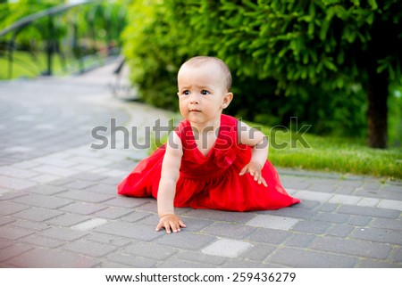 beautiful little girl in a spring park in red park - stock photo