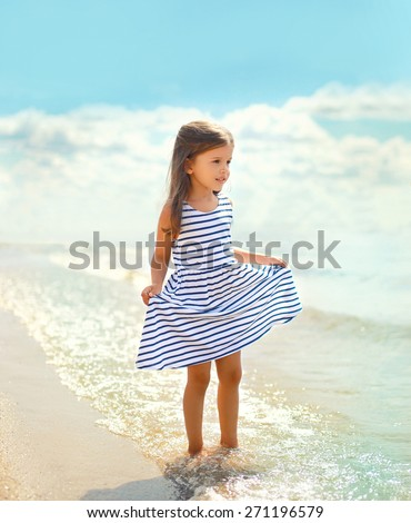 Beautiful little girl in a striped dress walking on the beach near sea, summer, vacation, travel - concept - stock photo