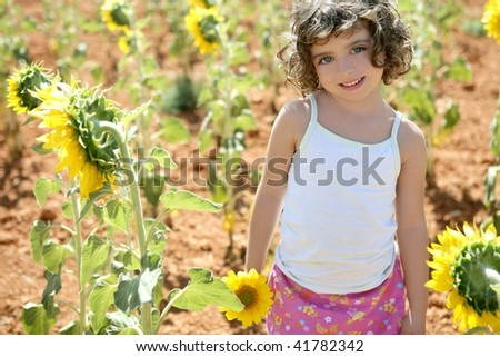 Beautiful little girl in a summer sunflower colorful field - stock photo