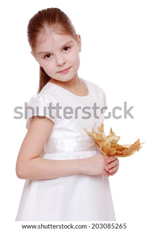Beautiful little girl in a white dress with charming smile holds decorative autumn leaves isolated on white