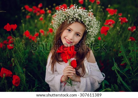 beautiful little girl in a wreath of poppies