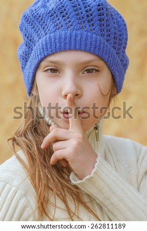 Beautiful little girl in blue beret calls for silence, put his finger to his mouth. - stock photo